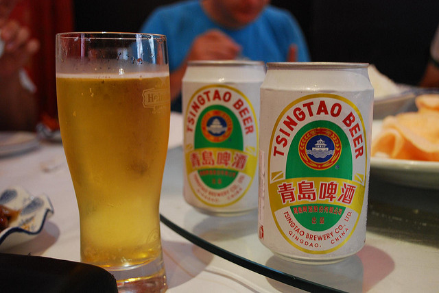 a glass filled with two cans of tsingtao beer