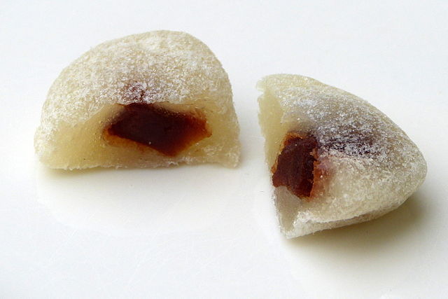 a piece of ai wo-wo sliced in half, exposing its sweet filling that makes it one of the most well-known Chinese New Year desserts