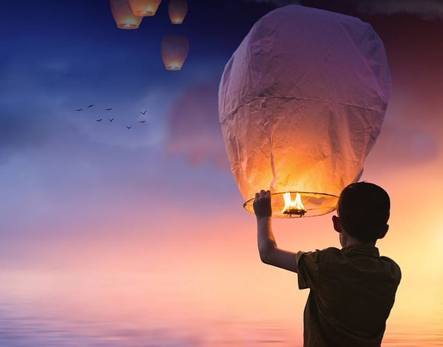 a boy about to release a kongming lantern into the sky