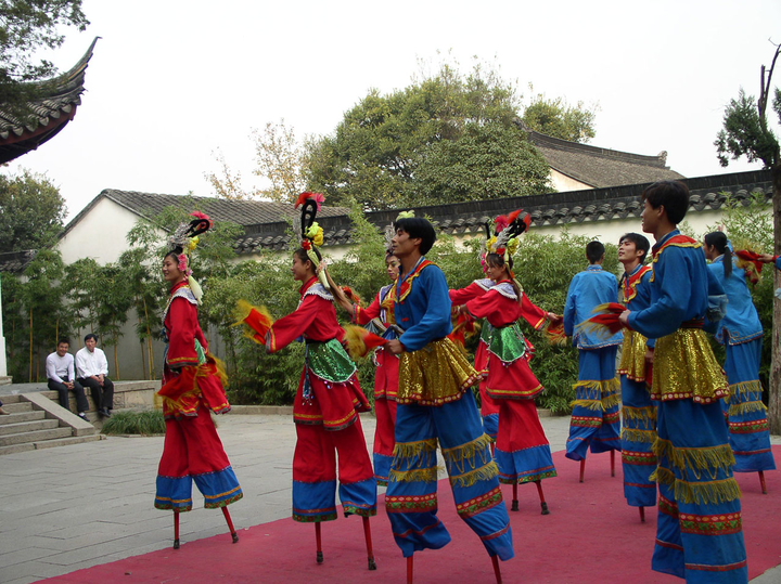 a group of performers in colorful costumes dancing on stilts