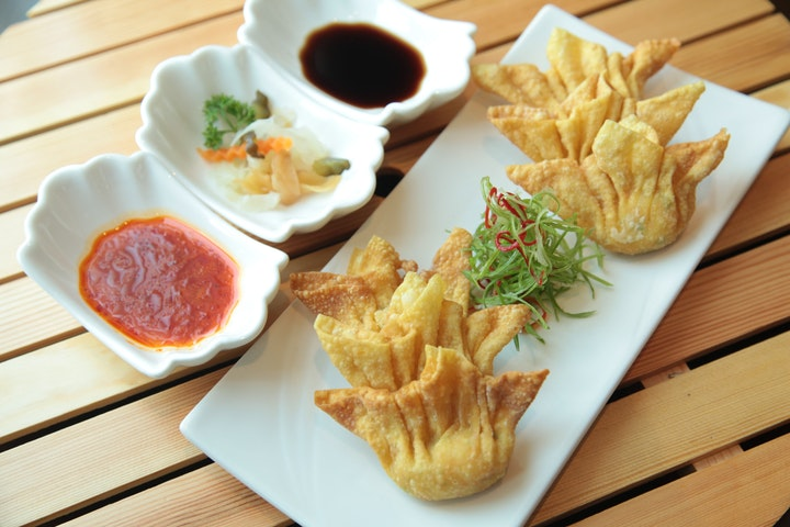 a plate of dumplings, the chinese new year food prepared with sauce and various vegetables