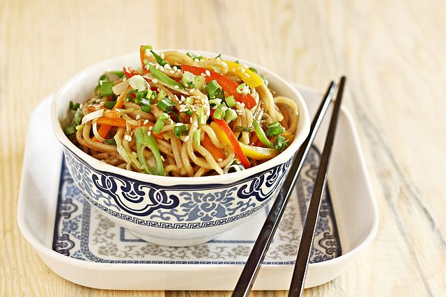 a bowl of hakka noodles cooked with various vegetables and topped with sesame seeds