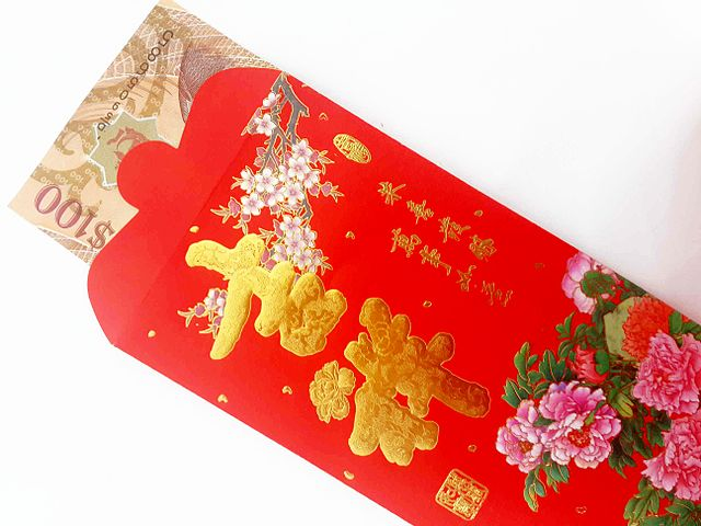 a chinese new year red pocket containing a hundred dollar bill