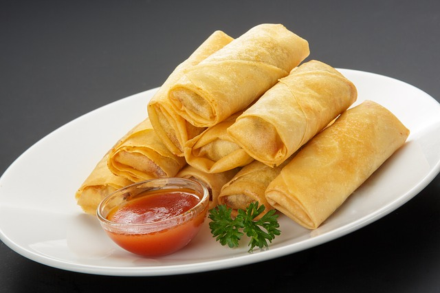 spring rolls served with sauce and a coriander leaf as garnish