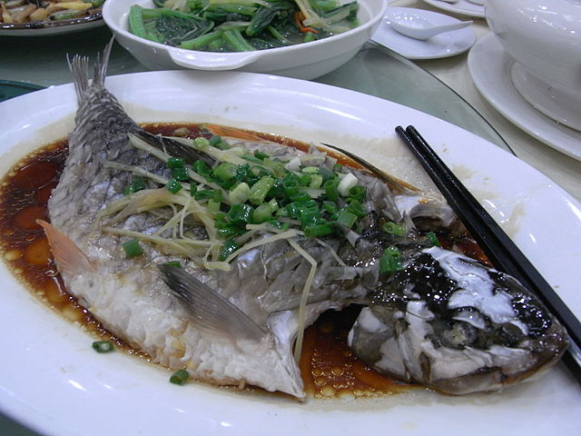 whole steamed fish topped with chopped onion leaves