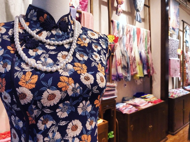a mannequin wearing modern qipao and a necklace of pearls displayed in a store